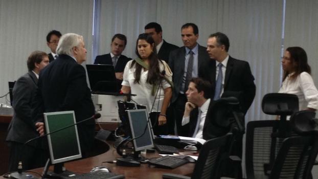 Auditores se reúnem ao redor de um computador para assistir à prova da Portuguesa
