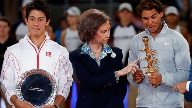 Kei Nishikori sorri, enquanto Rafael Nadal brinca com o troféu de Madri