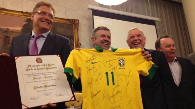 Valcke segura placa de título concedido a Blatter; ao lado de dele, o presidente da CBF, José Maria Marin, sorri