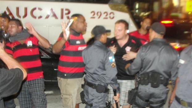 Policiais seguram torcedores do Flamengo após início de confusão: noite foi agitada no entorno do Maracanã